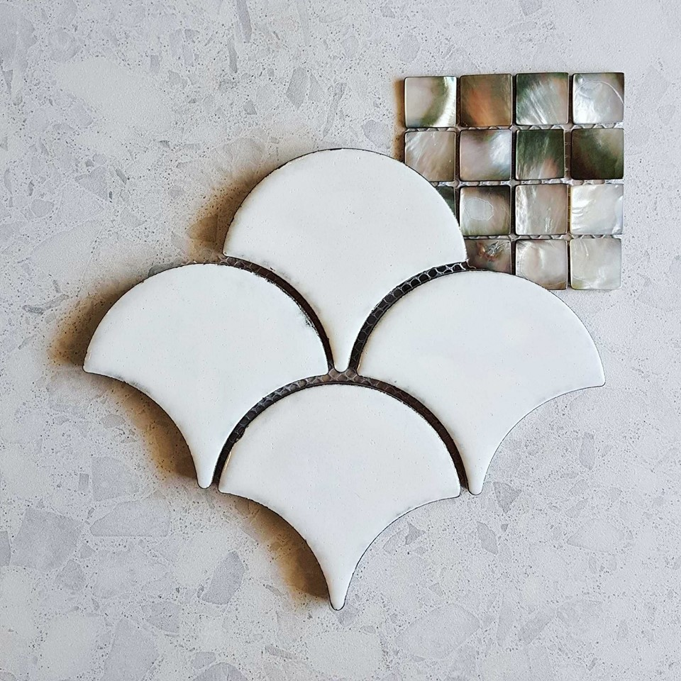 Antique white porcelain fishscale, black mother-of-pearl mosaic, and white Italian terrazzo; subtle glamour.
